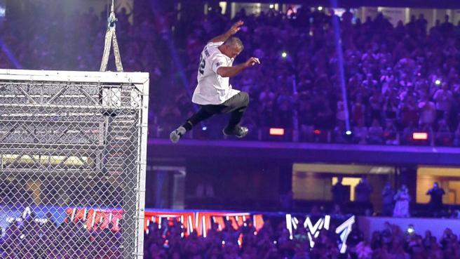 Shane McMahon jumps from the Cell and crashes through the announcers table image: wwe.com